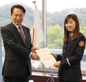 認証状を交付する尾花正啓市長と、受け取る平松加奈子さん