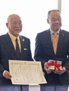 手帳の贈呈を受けた原教育長と、感謝状を手にした西田代表理事(左)