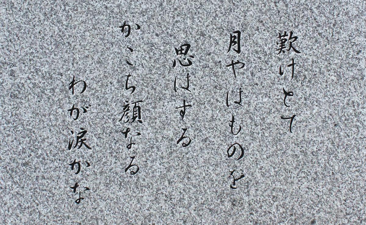 像の足元の石碑に刻まれた、西行の恋の歌